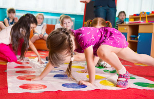 Cute toddlers playing in twister game at kindergarten